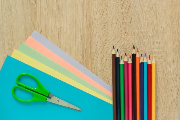 Vista dall'alto di carta multicolore, matite e forbici sul tavolo di legno