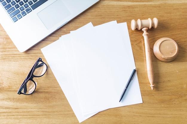Vista dall'alto di carte bianche; martelletto per laptop; occhiali e penna su fondo in legno