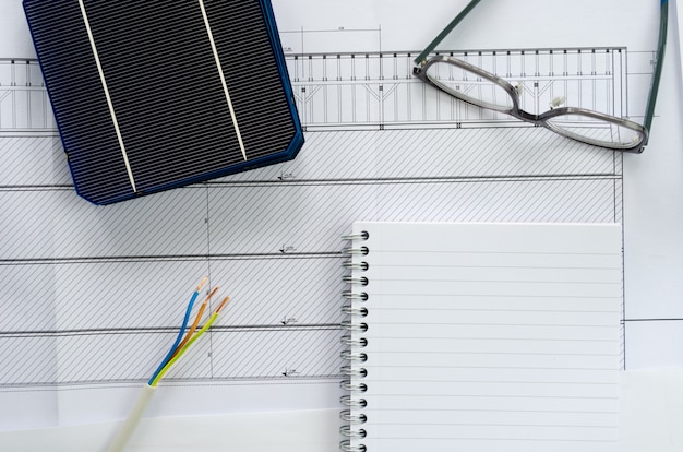 Vista dall'alto di celle solari, blocco note, occhiali e cavo elettrico come concetto di pianificazione per il progetto fotovoltaico