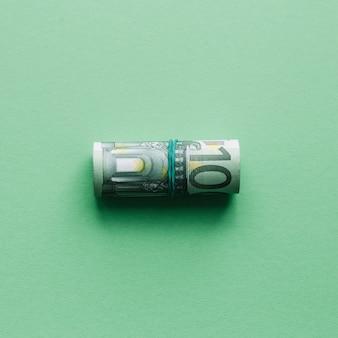 Vista dall'alto di cento euro banconote arrotolate sulla superficie verde