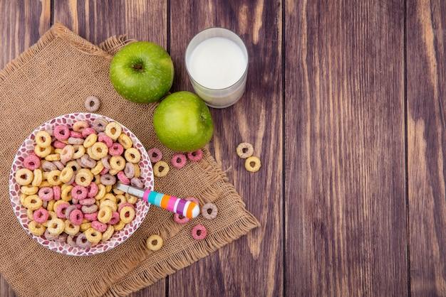 Vista dall'alto di cereali colorati sulla ciotola con un cucchiaio con un bicchiere di latte con mele verdi sul panno del sacco su legno