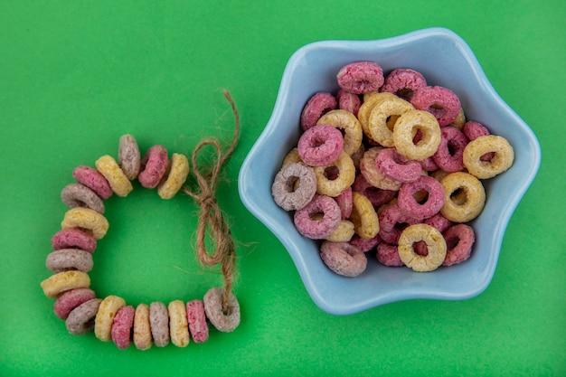 Vista dall'alto di cereali multicolori su una ciotola a forma di stella con cereali disposti su una collana sulla superficie verde