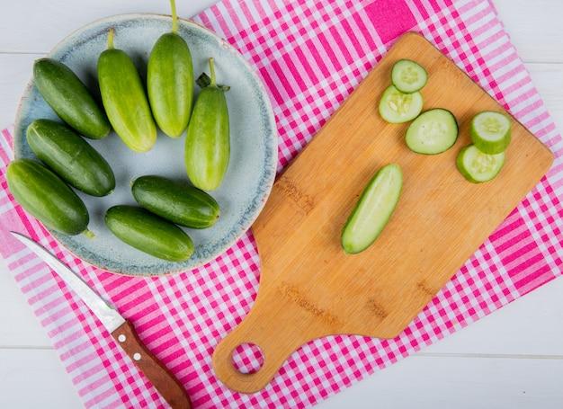 Vista dall'alto di cetrioli tagliati e affettati sul tagliere con quelli interi nel piatto e coltello sul panno plaid e legno