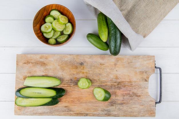 Vista dall'alto di cetriolo affettato e tagliato sul tagliere con ciotola di fette di cetriolo e cetrioli fuoriuscita dal sacco su legno