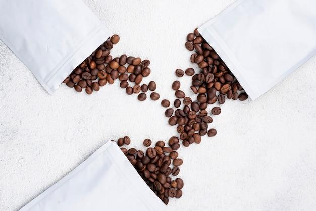 Vista dall'alto di chicchi di caffè con sacchetti bianchi