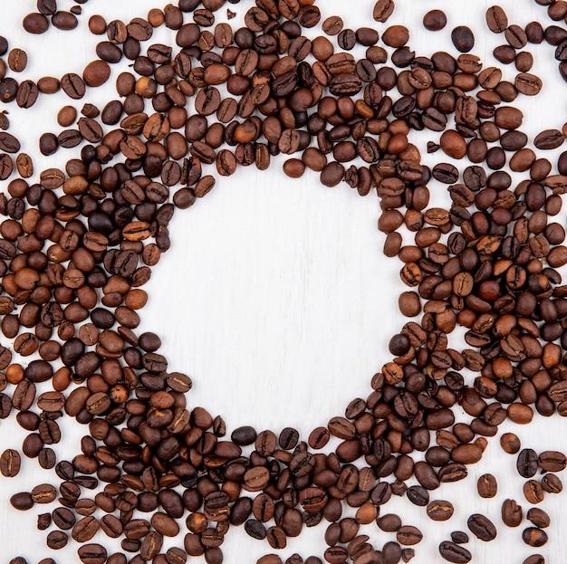 Vista dall'alto di chicchi di caffè tostati scuri isolati su una forma circolare su uno sfondo bianco con spazio di copia