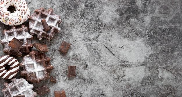 Vista dall'alto di cialde con cioccolato e ciambelle