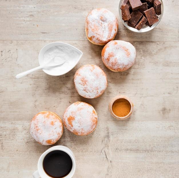 Vista dall'alto di ciambelle con zucchero a velo e pezzi di cioccolato