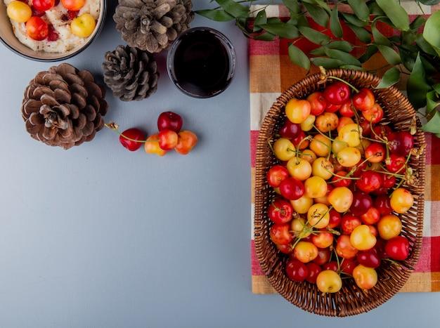 Vista dall'alto di ciliegie più piovose mature in un cesto di vimini un bicchiere di succo e coni su grigio con spazio di copia