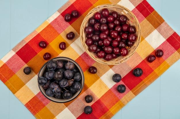 Vista dall'alto di ciliegie rosse fresche su un secchio con prugnole viola scuro su una tovaglia a quadri su sfondo blu