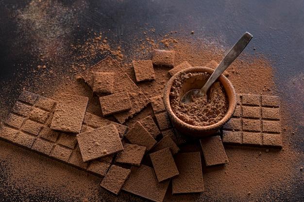 Vista dall'alto di cioccolato con una ciotola di cacao in polvere