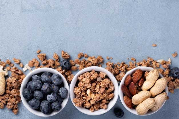 Vista dall'alto di ciotole con cereali per la colazione e assortimento di noci e mirtilli
