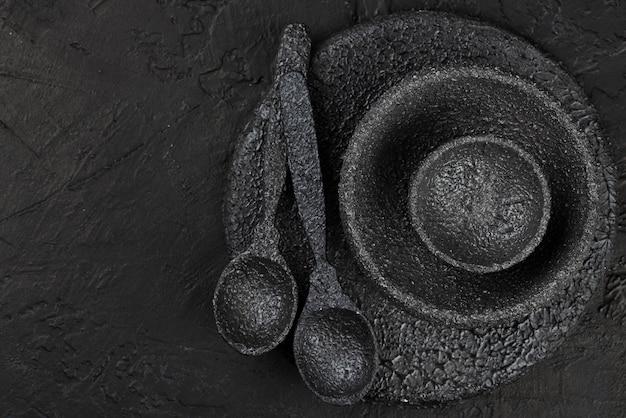 Vista dall'alto di ciotole di pietra nera e cucchiai