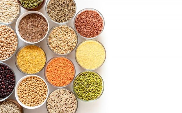 Vista dall'alto di ciotole di vetro con cereali, fagioli e semi