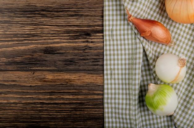 Vista dall'alto di cipolle come scalogno dolce e bianco su panno plaid e sfondo in legno con spazio di copia