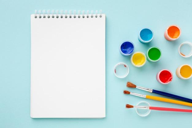 Vista dall'alto di colorati aquarelle e notebook