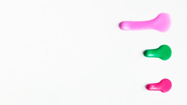 Vista dall'alto di colore smalto per unghie campione isolato su superficie bianca