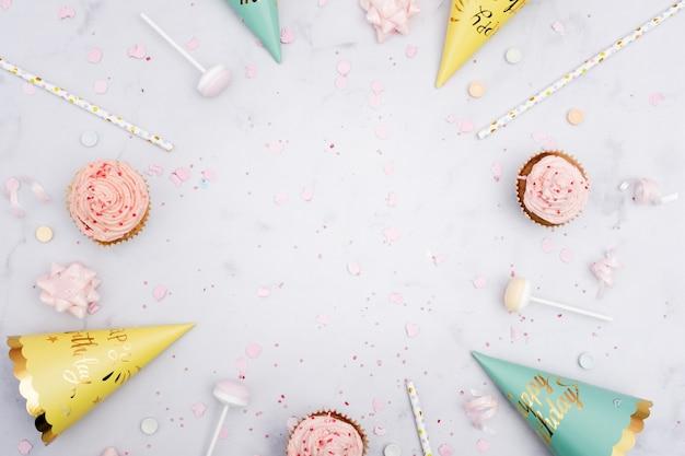 Vista dall'alto di coni di compleanno con cannucce e cupcakes