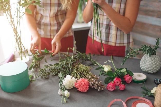 Vista dall'alto di consegna fiori. fioristi che creano ordine, realizzano bouquet di rose nel negozio di fiori. due fioriste femminili stanno facendo mazzi di fiori. una donna che raccoglie rose per un mazzo, anche un'altra ragazza lavora.