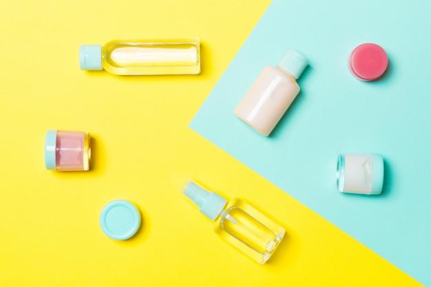 Vista dall'alto di contenitori cosmetici, spray, vasetti e bottiglie su giallo e blu. vista ravvicinata