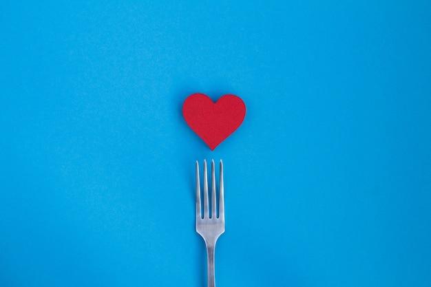 Vista dall'alto di cuore rosso e forchetta sul blu