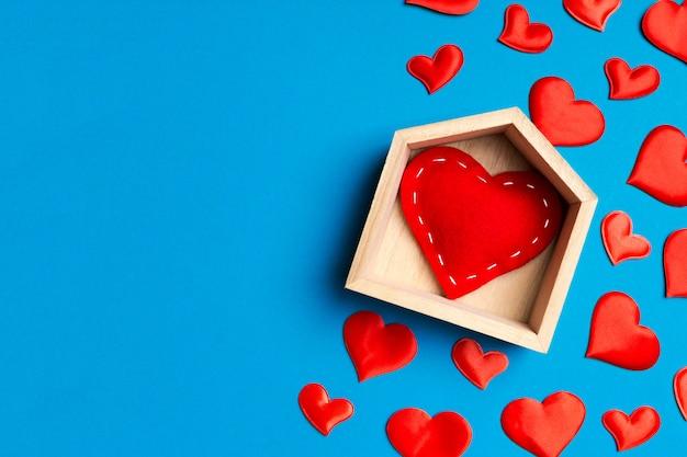 Vista dall'alto di cuore rosso in una casa circondata da piccoli cuori su sfondo colorato. concetto di casa dolce casa. san valentino