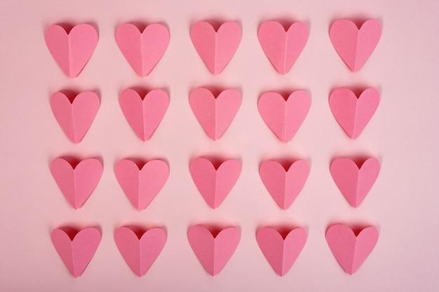 Vista dall'alto di cuori di carta rosa su sfondo rosa. cuori di carta astratti ritagliati disposti in file