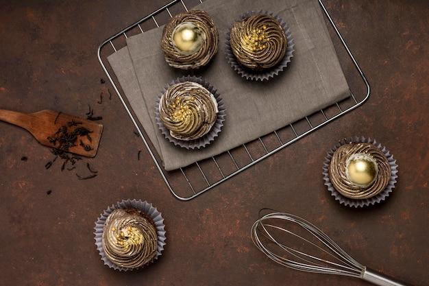 Vista dall'alto di cupcakes su rack di raffreddamento con frusta e spatola