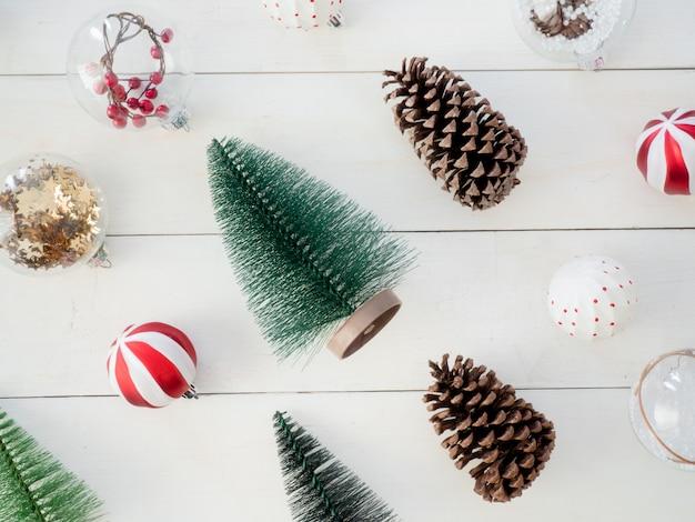 Vista dall'alto di decorazioni natalizie con pigne, albero giocattolo e palline