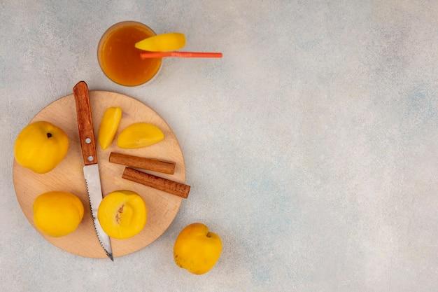 Vista dall'alto di deliziose pesche gialle su una tavola da cucina in legno con coltello con bastoncini di cannella su uno sfondo bianco con spazio di copia