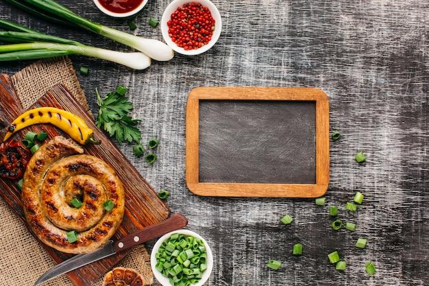 Vista dall'alto di deliziose salsicce alla griglia e ingrediente fresco con ardesia vuota sul fondale in legno