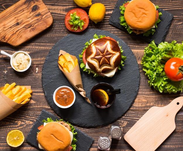 Vista dall'alto di deliziosi hamburger, con verdure, su una superficie di legno.