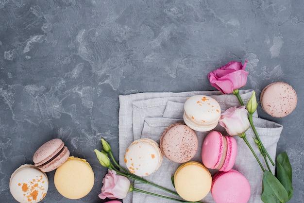 Vista dall'alto di deliziosi macarons con rose e copia spazio