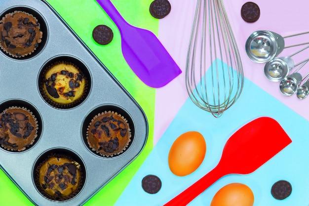 Vista dall'alto di deliziosi muffin vanila, caffè e cioccolato, biscotti e panna su colorato