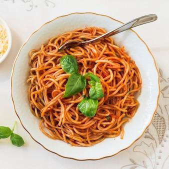 Vista dall'alto di deliziosi spaghetti con basilico sul piatto in ceramica