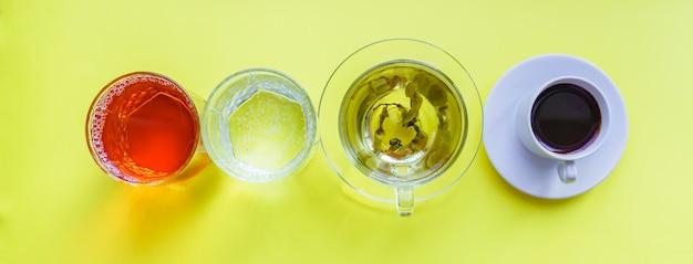 Vista dall'alto di diverse bevande - bere caffè, acqua frizzante, succo di mela e tè verde su backgeound giallo. vita sana e concetto di dieta