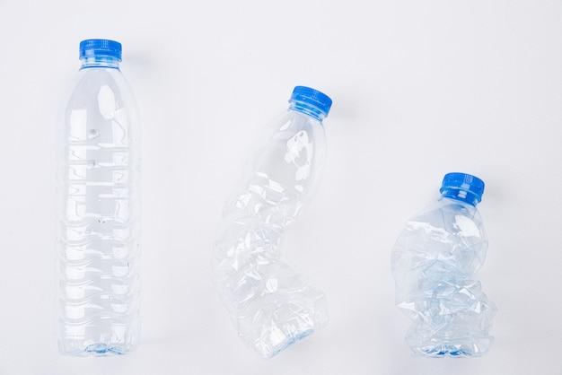 Vista dall'alto di diverse bottiglie di acqua vuota di plastica da pieno a schiacciato su bianco