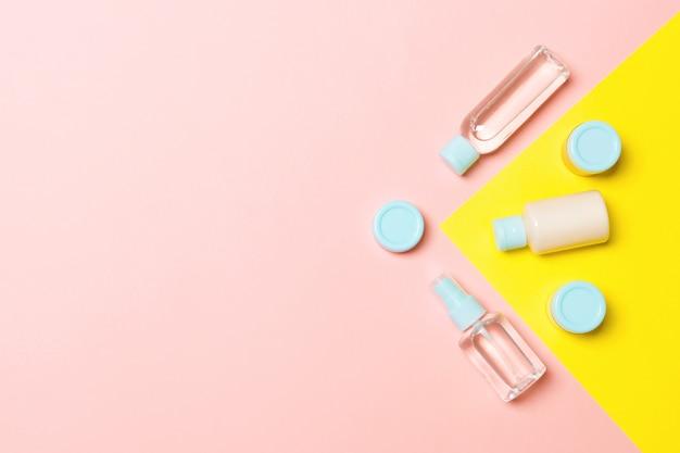 Vista dall'alto di diverse bottiglie di cosmetici e contenitori per cosmetici su rosa e giallo. composizione piatta laica con copyspace