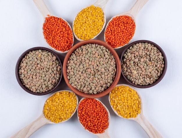 Vista dall'alto di diverse lenticchie in ciotole marroni e cucchiai di legno