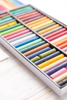 Vista dall'alto di diversi colori pastello vernice e pennarelli in scatole sul tavolo bianco