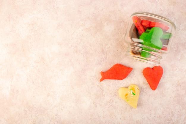 Vista dall'alto di diversi deliziosi biscotti colorati formati all'interno possono sulla superficie rosa