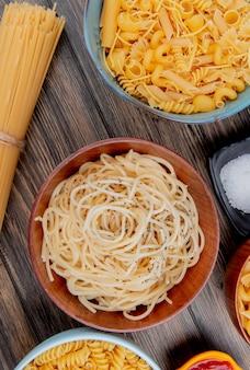 Vista dall'alto di diversi maccheroni come spaghetti rotini vermicelli e altri con sale e ketchup su legno
