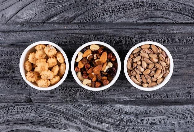 Vista dall'alto di diversi tipi di snack come noci e cracker in ciotole su orizzontale scuro