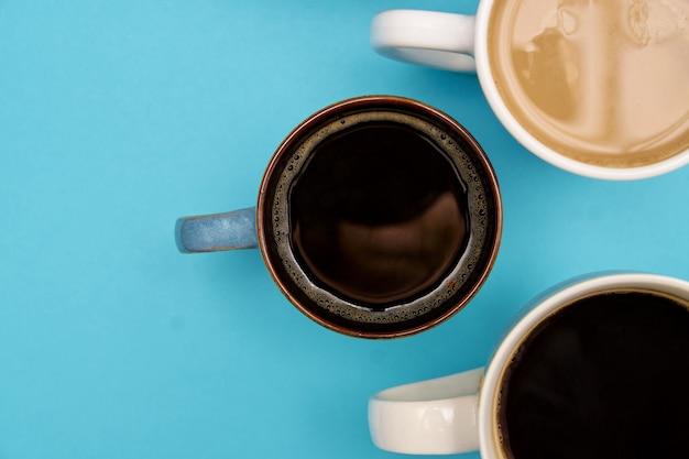 Vista dall'alto di diversi typrs di caffè caldo - nero e con latte su uno sfondo blu pastello. banner con