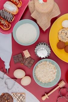 Vista dall'alto di dolci come torta biscotto al cioccolato con uova fiocchi d'avena e farina sul tavolo rosso