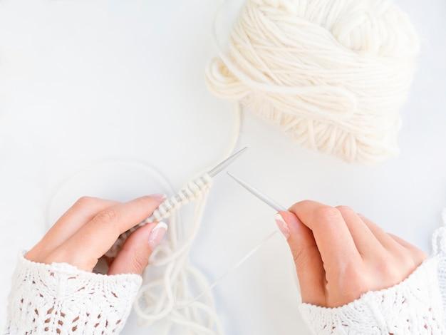 Vista dall'alto di donna all'uncinetto con lana bianca