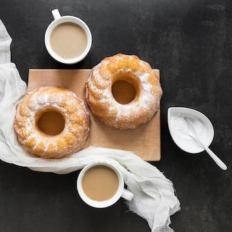 Vista dall'alto di due ciambelle con tessuto e caffè