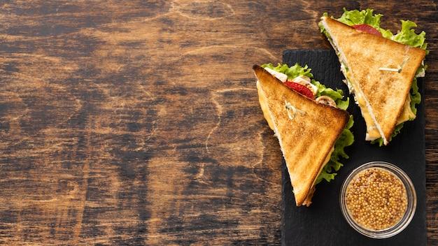 Vista dall'alto di due pomodori triangolo e panini con insalata con spazio di copia