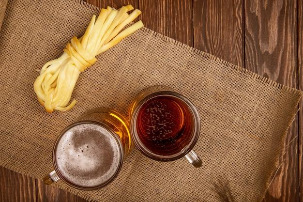 Vista dall'alto di due tazze di birra con formaggio a pasta filata su tela di sacco su rustico con spazio di copia