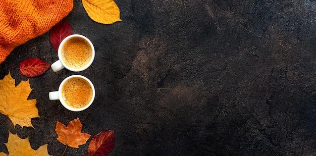 Vista dall'alto di due tazze di caffè intorno a foglie gialle